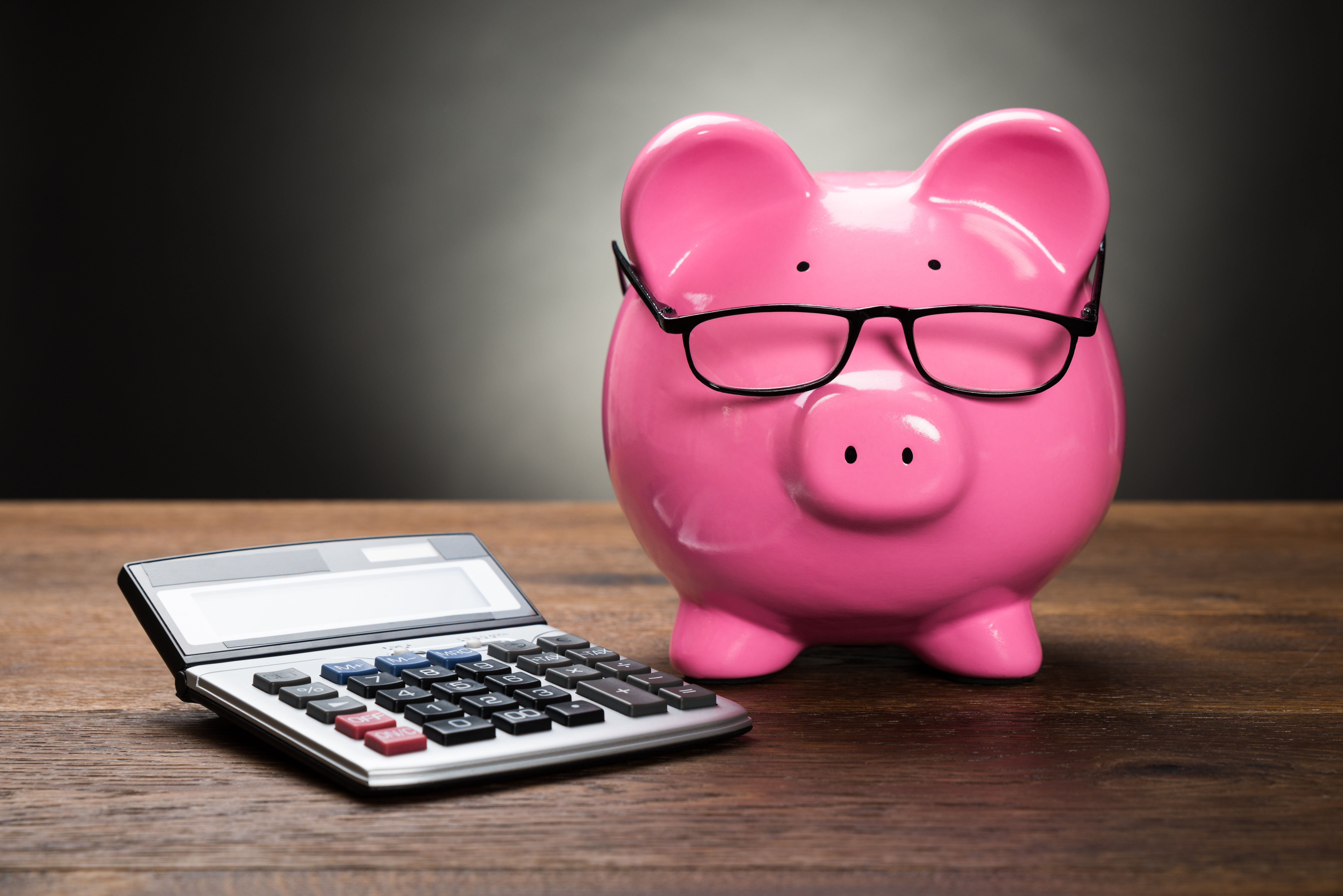 Pink Piggybank With Calculator On Wooden Table